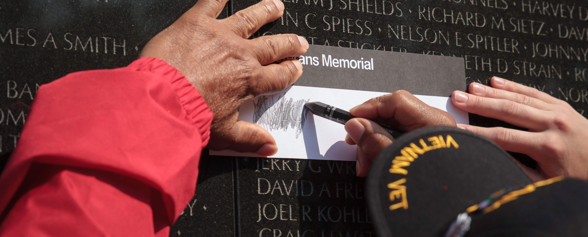 Vietnam Vet Creating a Rubbing on the Vietnam Wall